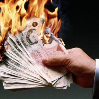 Man burning £50 notes.