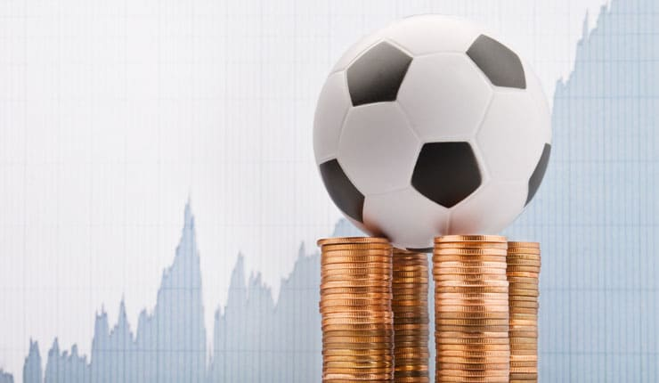 A football on top of coin stacks, with a profit graph in the background
