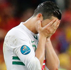 Cristiano Ronaldo holds his head in his hands after Portugal lose to Spain.