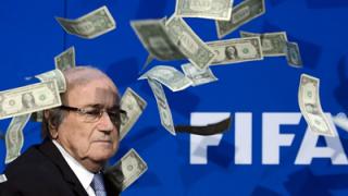 Comedian Simon Brodkin throws money over disgraced former FIFA president Sepp Blatter.