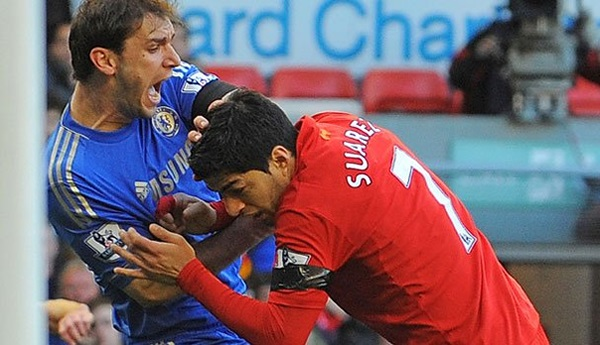 Chelsea's Branislav Ivanovic pushes Suarez away after he sunk his teeth in to his arm.