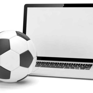 A football next to a laptop computer.