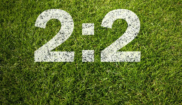 A football pitch with the score 2:2 written on it in white paint.