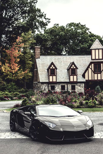 Matt black Lamborghini parked in the driveway of a mansion house.