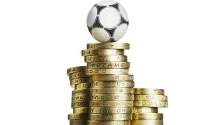 A pile of one pound coins with a football on top
