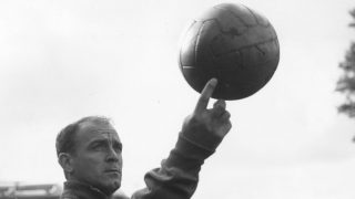 Real Madrid legend Alfredo Di Stefano holds up a football.