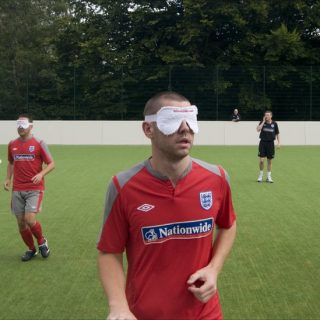 A Blind Football player stands on the field.