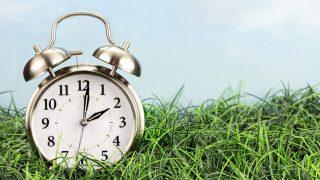 An alarm clock sitting on a grass football pitch.