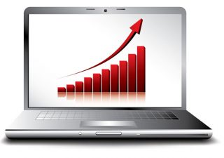 Laptop screen which shows a profit chart going up.