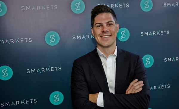 Smarkets.com founder Jaston Trost stands in front of the company logo.
