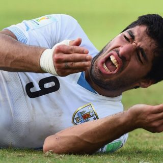 Luis Suarez puts his hand to his mouth in pain after biting Giorgio Chiellini at the 2014 World Cup.