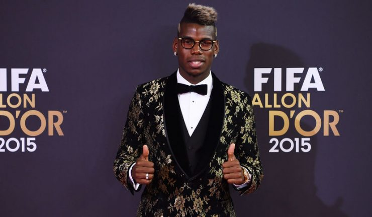 Paul Pogba poses with his thumbs up in front of the 2015 Ballon dOr logo.