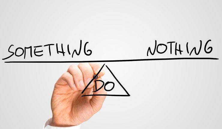"""Man writing black text """"do something"""", """"do nothing"""""""