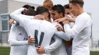 Real Madrid Castilla players huddle together after scoring a goal.