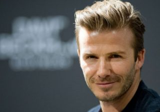 David Beckham smiles at the camera.