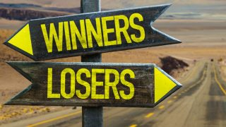 Desert road with signpost directing Winners and Losers