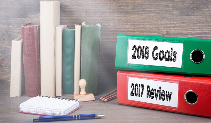 "Two folders on a desk labelled ""2017 review"" and ""2018 goals"""
