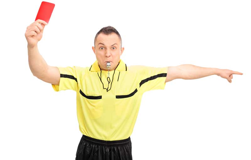 A football referee holding up a red card