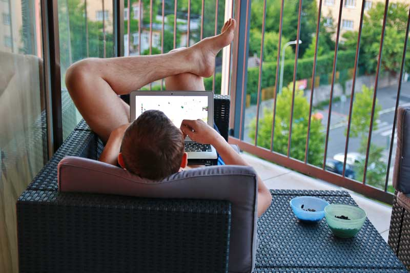 A naked man playing with his laptop computer.