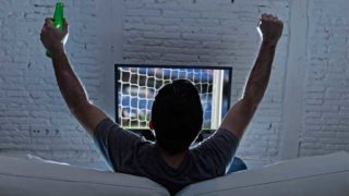 A man holding a bottle of beer, watching a football match on television and celebrating a goal