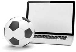 A football next to a laptop computer, which represents football trading.