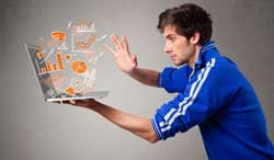 Man wearing a football shirt and holding a laptop which has statistics coming out of it.