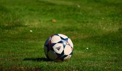 An Adidas branded football sits on a grass football pitch.